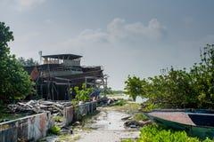 Rue de village avec la route boueuse et le bateau cassé à l'île de Fenfushi Photo libre de droits