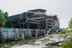 Rue de village avec la route boueuse et le bateau cassé à l'île de Fenfushi Photographie stock libre de droits