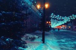 Rue européenne de ville de nuit d'hiver avec des guirlandes entre les piliers Les lanternes s'allument du côté gauche avant la no Image stock