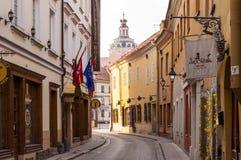 Rue incurvée médiévale avec des drapeaux de boutiques et logos dans la vieille ville de Vilnius Lithuanie Image stock