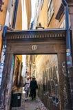 Rue médiévale étroite superbe avec la porte en bois d'entrée de voûte, personnes de marche, façades jaune-orange criquées minable image libre de droits