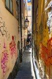 Rue médiévale étroite superbe complètement de graffiti, personnes de marche, façades jaune-orange criquées minables de bâtiments  photos libres de droits