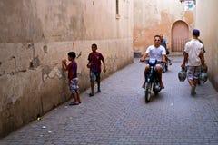 Rue passante à la ville historique avec les personnes locales avec des vases et de jeunes garçons sur une motocyclette images stock
