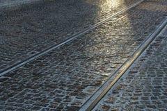 Rue pavée en cailloutis avec des longerons de tramway Photos stock