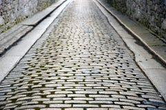 Rue pavée en cailloutis murée par pierre Images stock