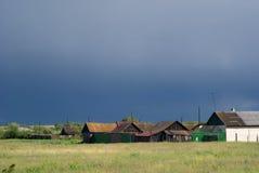 Rue russe de village dans un ciel nuageux sombre Photographie stock