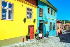 Rue saxonne médiévale avec les bâtiments colorés dans Sighisoara, la Transylvanie, Roumanie images libres de droits
