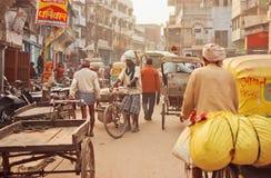 Rue serrée avec des travailleurs et des cyclistes de cargaison conduisant par les vieux bâtiments Image libre de droits
