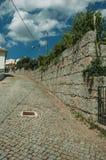 Rue sur une pente avec la porte de mur en pierre et de fer photos libres de droits