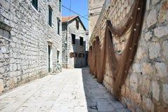 Rue tirée dans la vieille ville Hvar, Croatie avec des filets de pêche image libre de droits