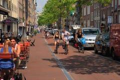 Rue typique de CA Amsterdam avec des cyclistes et des cafés, Hollande, Ne Photographie stock libre de droits