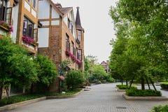 Rue verdoyante avant le bâtiment de style européen Photographie stock