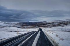Rue vide avec le paysage islandais pendant l'heure d'or de lever de soleil Image stock