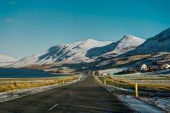 Rue vide avec le paysage islandais pendant l'heure d'or de lever de soleil Images stock