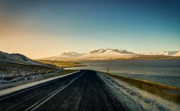 Rue vide avec le paysage islandais pendant l'heure d'or de lever de soleil Photographie stock