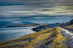 Rue vide avec le paysage islandais pendant l'heure d'or de lever de soleil Photos stock