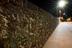 Rue vide la nuit avec un vieux mur de roche et des réverbères brûlant lumineux Image libre de droits