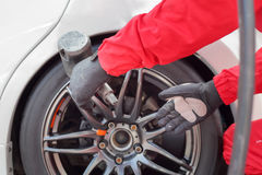 Rueda cambiante del coche de competición del mecánico de automóviles imagen de archivo