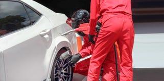 Rueda cambiante del coche de competición del mecánico de automóviles imagenes de archivo