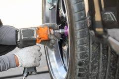 Rueda cambiante del coche de competición del mecánico de automóviles foto de archivo libre de regalías
