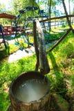 Rueda de agua del metal Barril de madera con el agua potable Imágenes de archivo libres de regalías