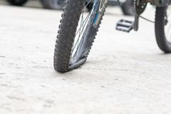 Rueda de bicicleta con el neumático plano en el camino concreto Fotos de archivo libres de regalías