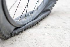 Rueda de bicicleta con el neumático plano en el camino concreto Imágenes de archivo libres de regalías