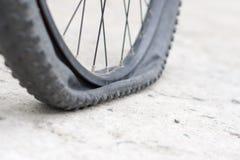 Rueda de bicicleta con el neumático plano en el camino concreto Foto de archivo libre de regalías