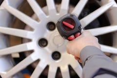 Rueda de cambio del mecánico en el coche con una llave Imágenes de archivo libres de regalías