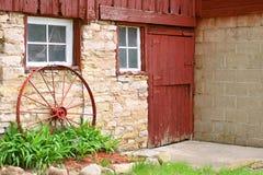 Rueda de carro antigua que se inclina en la pared de piedra vieja del granero foto de archivo