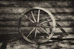 Rueda de carro rota vieja en la pared Imagen de archivo