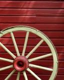 Rueda de carro vieja con la pared roja Imagen de archivo