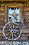 Rueda de carro vieja en la pared Fotografía de archivo