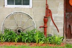 Rueda de carro y bomba de agua de madera antiguas por el granero imagen de archivo