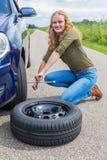 Rueda de coche cambiante de la muchacha holandesa en la carretera nacional Fotografía de archivo