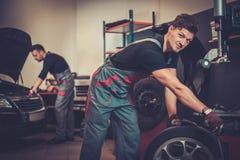 Rueda de coche de equilibrio profesional del mecánico de coche en el balanceador en servicio de reparación auto Foto de archivo