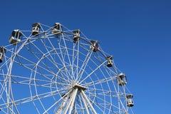 Rueda de Ferris contra el cielo azul brillante Fotos de archivo