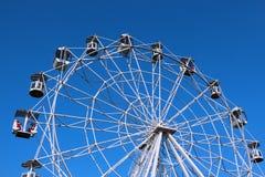 Rueda de Ferris contra el cielo azul brillante Foto de archivo