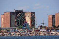Rueda de la maravilla en la playa en el parque de Coney Island con los nadadores y los persona que toma el sol en frente en Nueva imagen de archivo libre de regalías