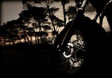 Rueda de la motocicleta en puesta del sol Fotografía de archivo libre de regalías