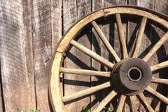 Rueda de madera contra granero Foto de archivo