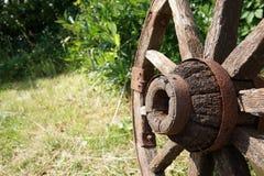 Rueda de madera en un fondo de la hierba verde fotografía de archivo