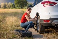 Rueda de repuesto cambiante del coche de la mujer joven en el camino abandonado en el campo Imágenes de archivo libres de regalías