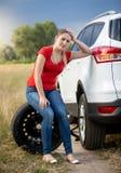 Rueda de repuesto triste del coche de la mujer que se sienta joven en el camino abandonado en el campo Imagen de archivo