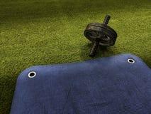 Rueda del ABS en hierba artificial verde y la estera de entrenamiento azul fotos de archivo libres de regalías