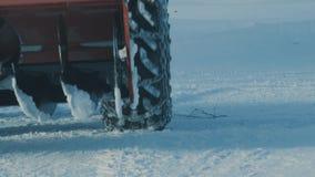 Rueda del tractor con la cadena en ella que se mueve en la nieve profunda almacen de metraje de vídeo