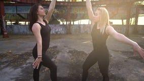Rueda en cámara en dos mujeres en un edificio abandonado que es ocupado por la acrobacia aérea en el anillo metrajes