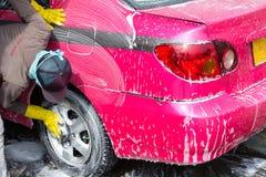 Rueda que se lava del trabajador del coche del taxi con espuma Fotos de archivo libres de regalías