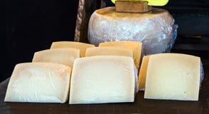 Rueda sana deliciosa fresca del queso, con varias rebanadas del queso en primero plano y fondo oscuro imagen de archivo