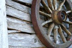 Rueda vieja de Spoked en una pared de madera Fotografía de archivo